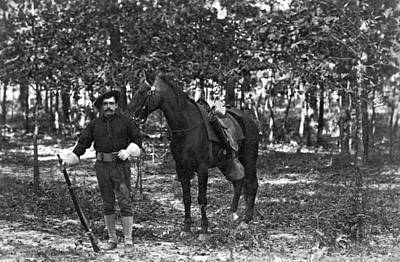 Turn Of The Century Photograph - A Member Of The Cavalry Poses Standing In Front Of His Horse by Underwood Archives