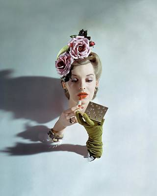 Indoors Photograph - A Model Applying Lipstick by John Rawlings
