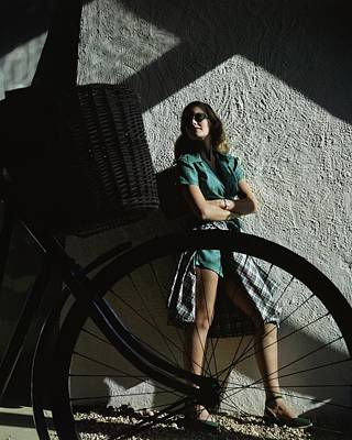 1940s Fashion Photograph - A Model Behind A Bicycle by John Rawlings