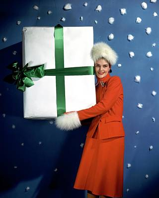 Photograph - A Model Carrying A Large Wrapped Gift by John Rawlings