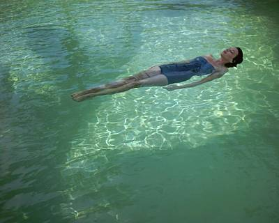 Ripples Photograph - A Model Floating In A Swimming Pool by John Rawlings
