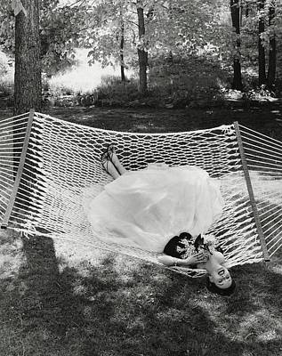 Dress Photograph - A Model Lying On A Hammock by Gene Moore