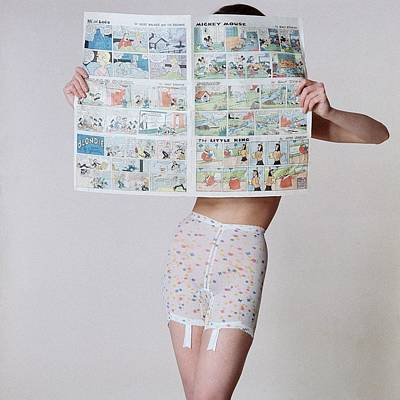 Studio Shot Photograph - A Model Wearing A Girdle With A Comic by Louis Faurer