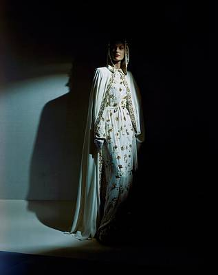 Photograph - A Model Wearing A Hooded Ivory Cape Over An Ivory by Horst P. Horst