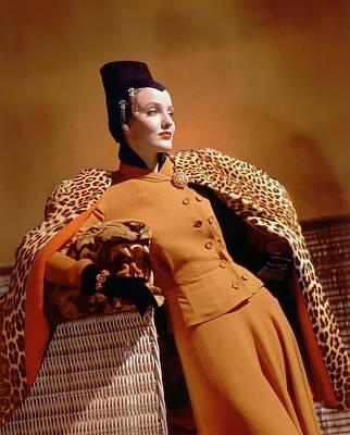 A Model Wearing A Leopard Print Cape And Orange Art Print
