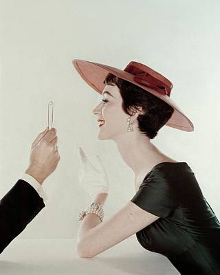 A Model Wearing A Sun Hat And Dress Print by John Rawlings