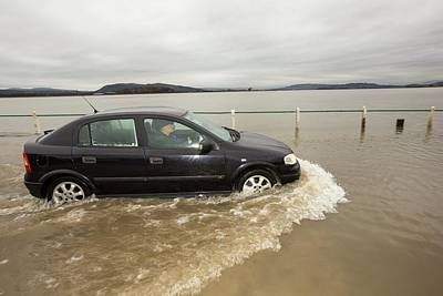Floods Photograph - A Motorist Travels Through Flood Waters by Ashley Cooper