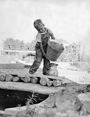Young Boy Photograph - A Small Boy On A Farm Pours Water From A Bucket Into A Pitcher F by Underwood Archives