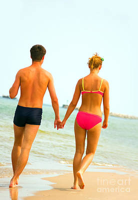 Boyfriend Photograph - A Teenage Couple Walking On The Beach by Michal Bednarek