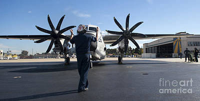 Greyhound Photograph - A  U.s. Sailor Signals To A C-2a by Stocktrek Images