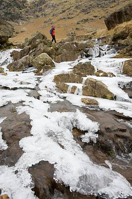 Winter Landscapes Photograph - A Walker Crosses A Frozen Beck by Ashley Cooper