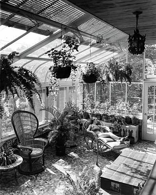A Woman Resting On A Chair Inside A Greenhouse Art Print by Eric J. Baker
