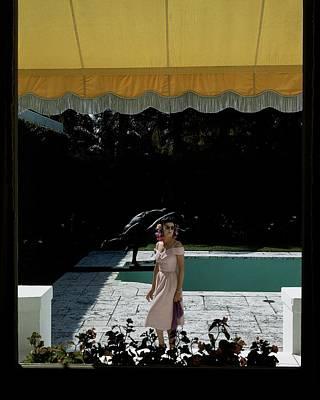 Florida House Photograph - A Woman Walking Beside Her Swimming Pool by John Rawlings