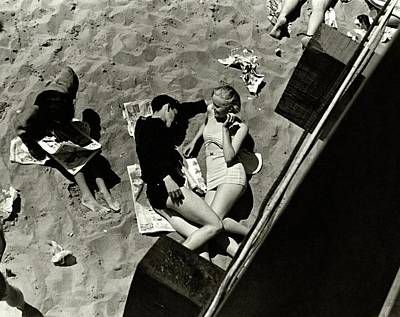 Coney Island Photograph - A Young Couple Lying On A Beach by Lusha Nelson
