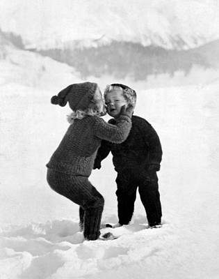 A Young Girl Gives Her Little Brother A Kiss On The Cheek In The Snow Art Print