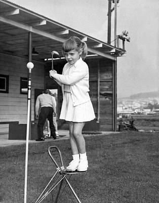 A Young Girl Hits A Golf Ball Art Print by Underwood Archives