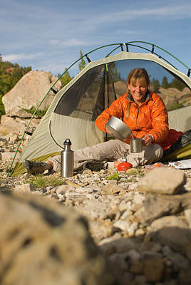 Hobbies And Collections - Art And Photograph - A Young Woman Cooks At Her Tent While by Jeff Diener