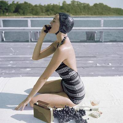 Healthy Eating Photograph - A Young Woman Wearing A Swimsuit Eating Grapes by John Rawlings