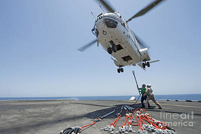 Airmen Attach A Cargo Hook To An Art Print by Stocktrek Images