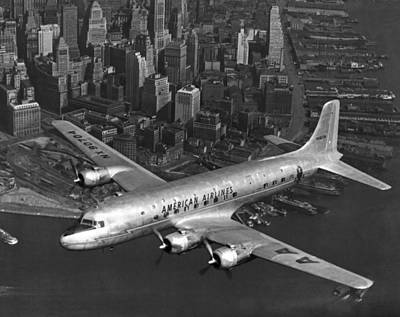 Building Exterior Photograph - American Dc-6 Flying Over Nyc by Underwood Archives