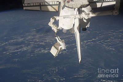 An Astronaut Carries A Pump Module Art Print by Stocktrek Images