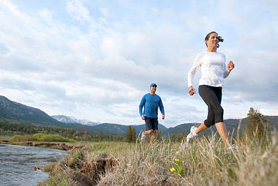 Cross-cap Photograph - An Athletic Couple Trail Running by Corey Rich