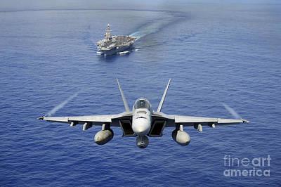 An Fa-18e Super Hornet Flying Above Uss Art Print by Stocktrek Images
