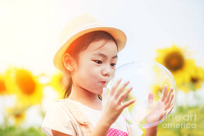 Asian Little Girl Is Blowing A Soap Bubbles In Sunflower Garden Art Print by Anek Suwannaphoom