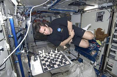 Astronaut Chess Game On The Iss Art Print by Science Photo Library