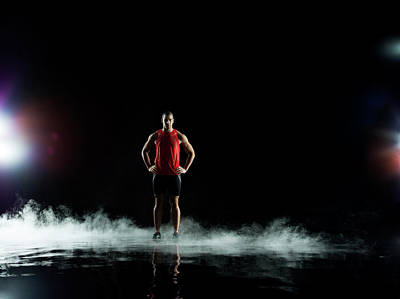 Photograph - Athelete Standing In Water At Night by Jonathan Knowles