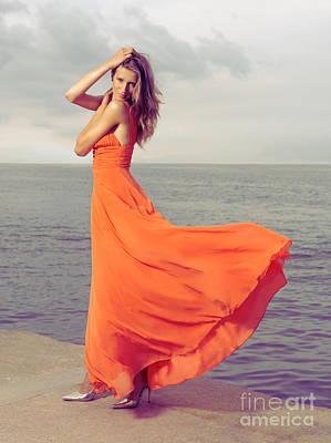 Flutter Photograph - Beautiful Woman In Orange Dress On Sea Shore by Oleksiy Maksymenko