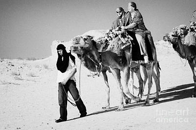 bedouin guide in modern clothing leads british tourists riding camels and wearing desert clothes into the sahara desert at Douz Tunisia Art Print by Joe Fox