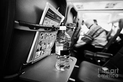 Passenger Plane Photograph - Bottle Of Water On Tray Table Interior Of Jet2 Aircraft Passenger Cabin In Flight Europe by Joe Fox