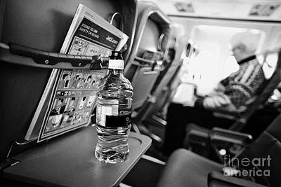 Passenger Plane Photograph - Bottle Of Water On Tray Table Interior Of Jet2 Aircraft Passenger Cabin In Flight by Joe Fox