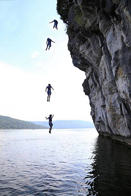 Photograph - Boy Jumping Off Cliff Into Water by Win-initiative
