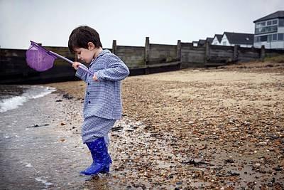 Net Photograph - Boy On Beach Holding Fishing Net by Ruth Jenkinson