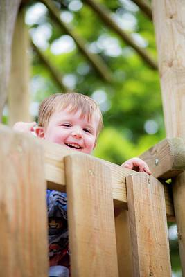 Candid Photograph - Boy Peeking Over Fence by Samuel Ashfield