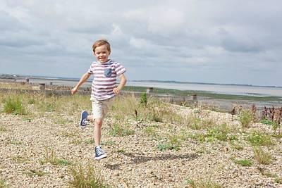 Boy Running On The Beach Art Print by Ian Hooton