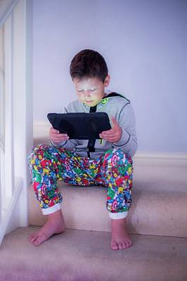 Boy Sitting On A Step Using A Tablet Art Print by Samuel Ashfield