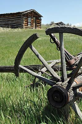 Wagon Wheel Hub Wall Art - Photograph - Broken Wagon Wheel And Log Building In Montana's Nevada City by Bruce Gourley