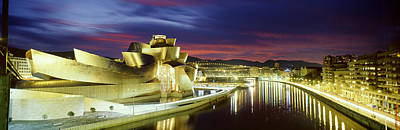 Gehry Photograph - Buildings Lit Up At Dusk, Guggenheim by Panoramic Images