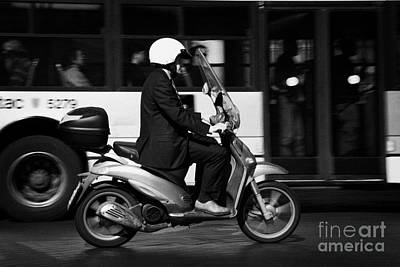 Business Man In Suit And White Helmet On Scooter Commutes Past Bus Full Of Passengers Through Piazza Art Print by Joe Fox
