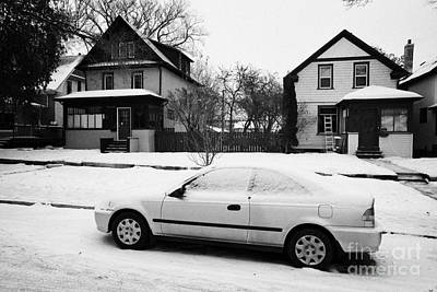 Sask Photograph - car covered in snow parked by the side of the street in front of residential homes caswell hill Sask by Joe Fox