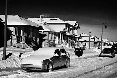 car covered in snow parked outside houses in the suburbs of Saskatoon Saskatchewan Canada Art Print by Joe Fox