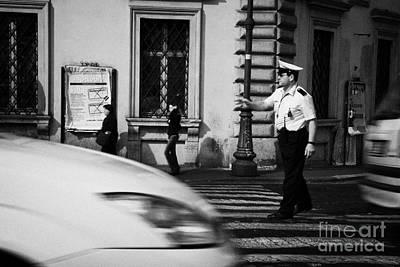 car drives across crossing as Roman Municipal policeman directs traffic at a pedestrian crossing in the Via Teatro Marcello Rome Lazio Italy Art Print by Joe Fox