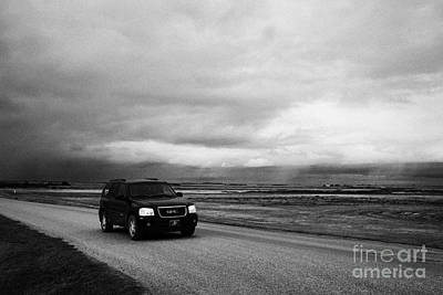 car driving on rural road as storm snow clouds forming over the prairies assiniboia Saskatchewan Can Art Print