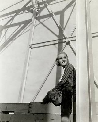 Carole Lombard Photograph - Carole Lombard Sitting On A Beam Of A Scaffolded by Cecil Beaton