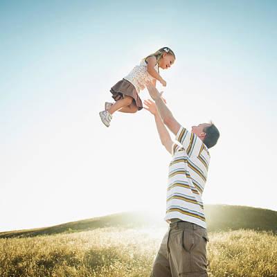 Caucasian Father Lifting Daughter Art Print by Erik Isakson