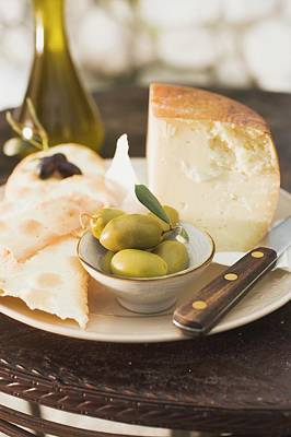 Cheese, Green Olives, Crackers And Olive Oil On Table Art Print