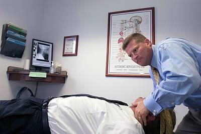 Chiropractor Manipulating Patient Art Print by Jim West